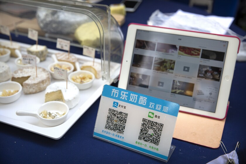 A card displaying QR codes to pay electronically with WeChat Pay and Alipay sits on a vendor's table at a farmer's market in Beijing, Tuesday, Oct. 27, 2020. China is accusing Washington of misusing national security as an excuse to hurt commercial competitors after President Donald Trump signed an order banning transactions with payment services Alipay and WeChat Pay and six other apps. (AP Photo/Mark Schiefelbein)