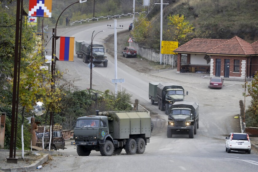 Green military trucks drive through a street in Stepanakert in Nagorno-Karabakh.