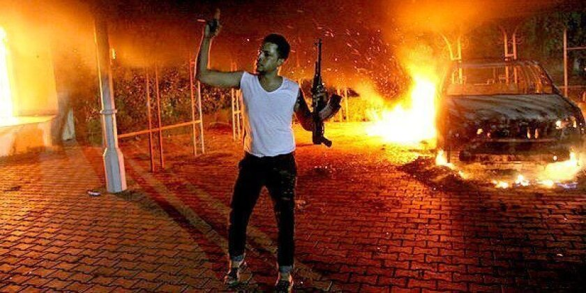 An armed man gestures as buildings and cars are engulfed in flames after being set on fire inside the U.S. consulate compound in Benghazi, Libya.