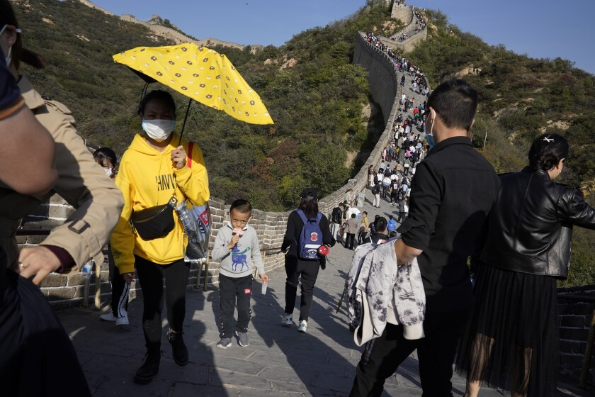FILE - In this Oct. 6, 2020, file photo, a child lowers his mask to enjoy an ice cream as he climbs up a stretch of the Badaling Great Wall of China on the outskirts of Beijing. Some 637 million Chinese tourists took domestic trips during the eight-day Golden Week holiday, spending the equivalent of tens of billions of dollars at a time when China is seeking to boost consumer spending to stimulate the economy. (AP Photo/Ng Han Guan, File)