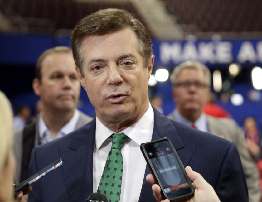 FILE - In this July 17, 2016 file photo, Trump Campaign Chairman Paul Manafort talks to reporters on the floor of the Republican National Convention at Quicken Loans Arena in Cleveland as Rick Gates listens at back left. Emails obtained by The Associated Press shed new light on the activities of a