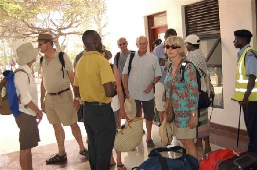 Foreign tourists wait to board charter flights after checking out of their hotels, at the airstrip on Manda Island, an island of the Lamu Archipelago, in Kenya Monday, Oct. 3, 2011. Nervous hotel owners there are urging Kenya's government to step up security in this area long popular with tourists and rich Kenyans, after last weekend's kidnapping of a French woman by Somali gunmen who travelled to the island by boat under the cover of darkness. (AP Photo)