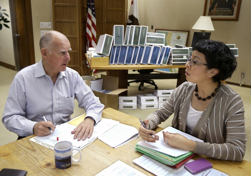 California Gov. Jerry Brown discusses a bill he is about to sign with Graciela Castillo-Kring his deputy legislative secretary, at his Capitol office in Sacramento, Calif.