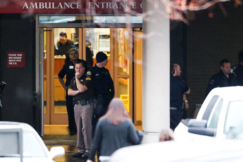 Officials wait outside Utah Valley Regional Medical Center in Provo following a shooting involving two law enforcement officers on Thursday, Jan. 30, 2014. (AP Photo/Daily Herald, Spencer Heaps)