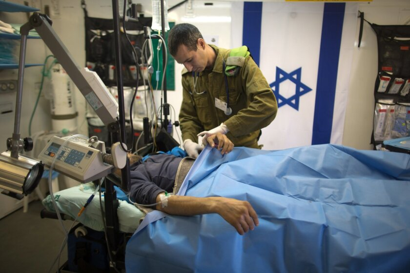 Israeli military medic tends  a Syrian man who was wounded in the ongoing violence in Syria, in a military hospital located in the Golan Heights near the border with Syria on Tuesday, Feb. 18, 2014. Since the Syrian conflict erupted almost three years ago hundreds of Syrians have received treatment