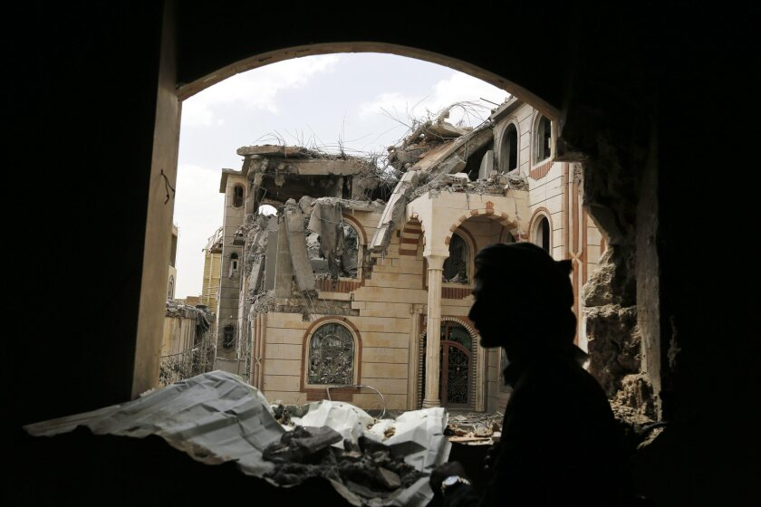 An armed Yemeni walks amid the ruins of a house belonging to an army commander loyal to the Houthi rebels in the capital, Sana, on July 6.