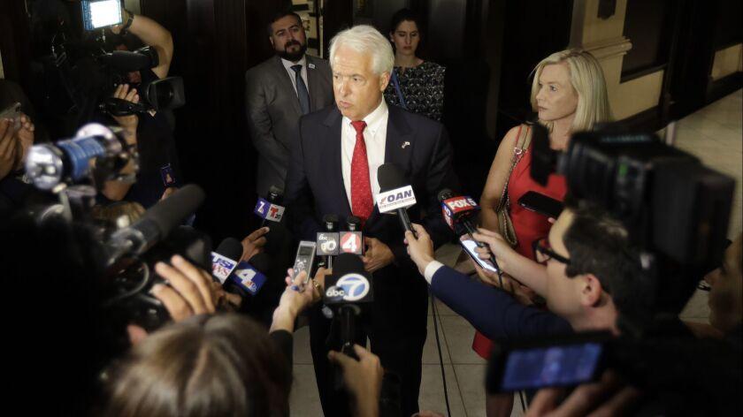 Republican gubernatorial candidate John Cox, center, speaks to reporters alongside his wife, Sarah Cox, in San Diego in June.