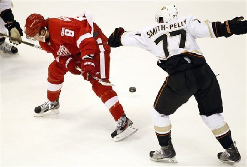Detroit Red Wings forward Justin Abdelkader (8) gets hooked by Anaheim Ducks forward Devante Smith-Pelly (77) and loses the puck during the first period of an NHL hockey game, Saturday, Nov. 5, 2011, in Detroit. (AP Photo/Tony Ding)