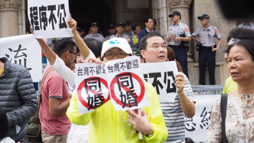 "People hold signs May 24 reading, ""Legal Procedure Unfair,"" ""Democracy Is Sacrificed"" and ""Taiwan Do"