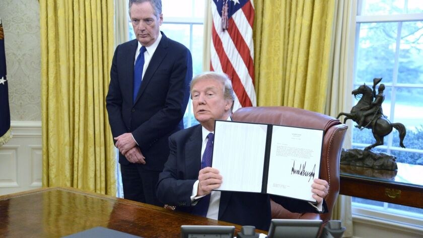 President Trump displays Section 201 action after signing it at the White House in Washington on Jan. 23. The administration is issuing tariffs on imported solar panels and washing machines.
