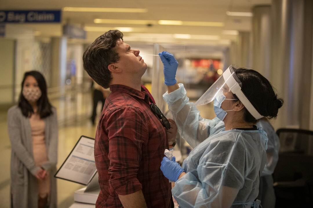 Elizabeth Cameros administers a deep nasal swab to traveler Wade Hopkins for coronavirus testing at LAX.