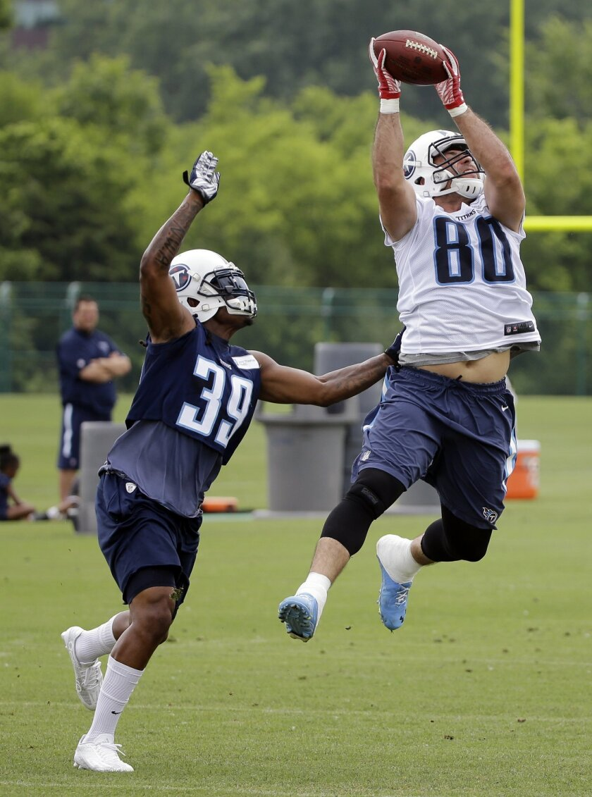 Tennessee Titans tight end Anthony Fasano (80) catches a pass as he is defended by safety Daimion Stafford (39) during an NFL football practice Thursday, May 26, 2016, in Nashville, Tenn. (AP Photo/Mark Humphrey)