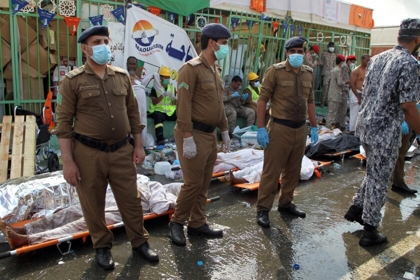 Saudi emergency personnel stand near bodies of Hajj pilgrims at the site where at least 717 were killed and hundreds injured in a stampede in Mina.