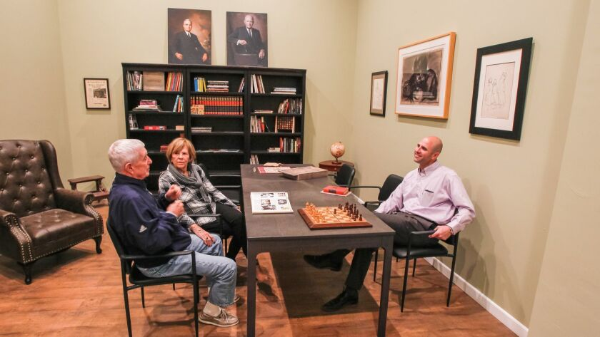 Bonita residents Bill and Sue Foley, left, sit with Scott Tarde, founder of Glenner Town Square, inside the Alzheimer's memory village's old-fashioned library, which is decorated with portraits of Presidents Truman and Eisenhower and a set of 1960 Collier's encyclopedias.