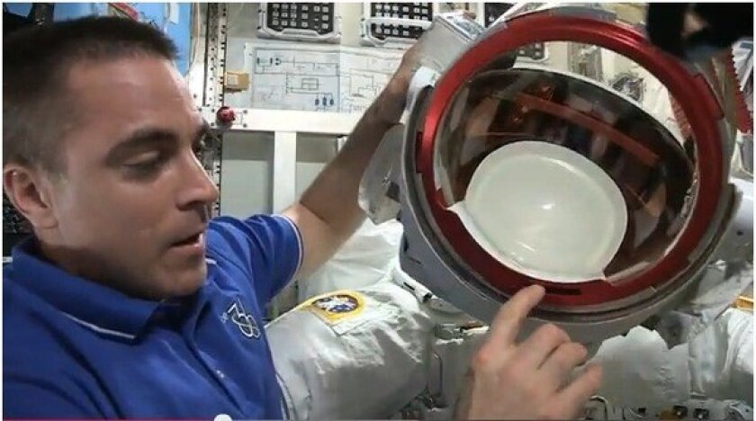 NASA astronaut Chris Cassidy explains the water leak in Italian astronaut Luca Parmitano's helmet during a spacewalk outside the International Space Station.