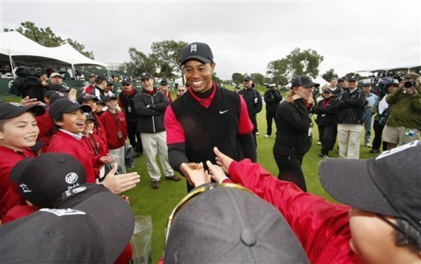 FILE - This is a Jan. 27, 2008, file photo showing Tiger Woods being congratulated by children from his Tiger Woods Learning Center, after his eight shot victory at the Buick Invitational golf tournament, in San Diego. Tiger Woods was different, or so he seemed, with his unmatchable talent and carefully burnished image of near-perfection. (AP Photo/Denis Poroy, File)