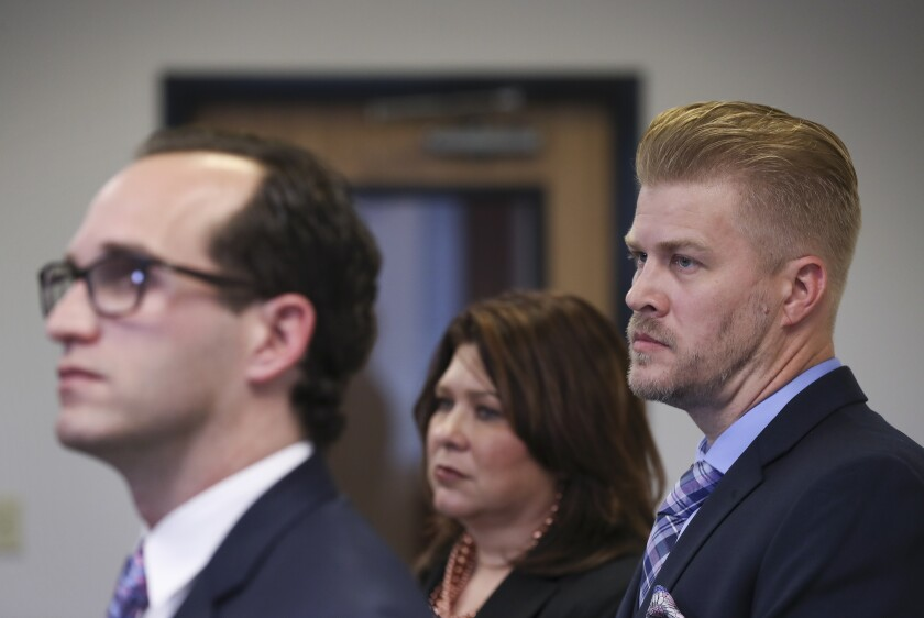 """FILE - In this Dec. 17, 2019, file photo, Patrick Baker, right, who recently pardoned by Kentucky Gov. Matt Bevin, right, and one of his attorneys Amy Robinson Staples, center, listen his other attorney Elliot Slosar, speaks during a press conference in Lexington, Ky. Baker, a convicted killer whose family had political connections to former Kentucky Gov. Matt Bevin, is back on trial for the 2014 killing that Bevin had pardoned him for shortly before leaving office. Baker now faces new federal charges in connection to Donald Mills' death, as authorities pointed to the """"dual sovereignty doctrine,"""" which allows state and federal officials to prosecute the same defendant for the same actions without infringing on double jeopardy protections. (Sam Upshaw Jr./Courier Journal via AP, File)"""