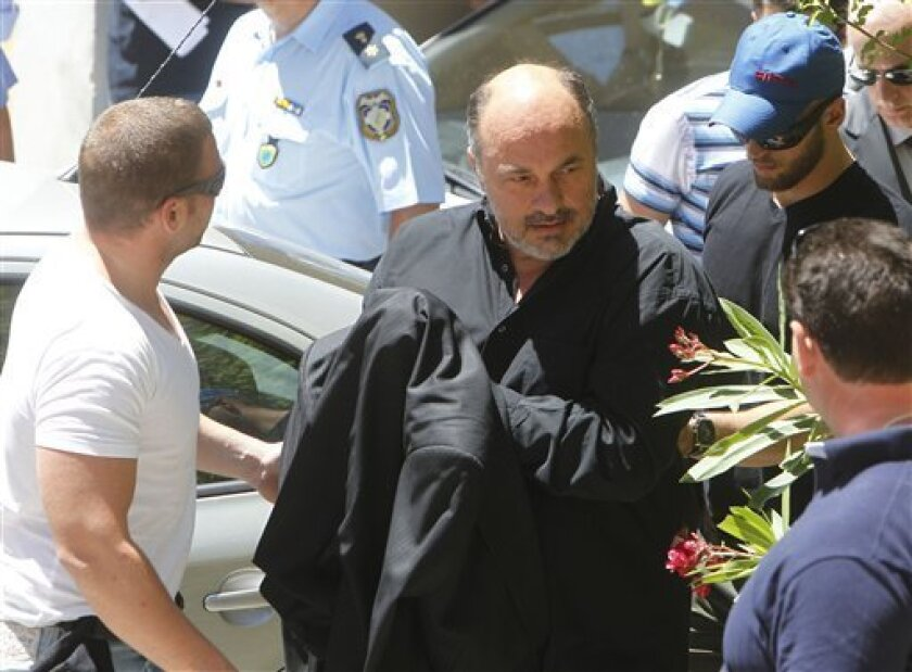 Achilleas Beos owner of the Greek Superleague soccer team Olympiakos Volos, escorted by police, arrives at a court in Athens, Thursday, June 23, 2011. Police in Greece say 10 people have been arrested as part of a match-fixing probe based on irregular betting patterns identified by European football's ruling body UEFA. (AP Photo/Thanassis Stavrakis)