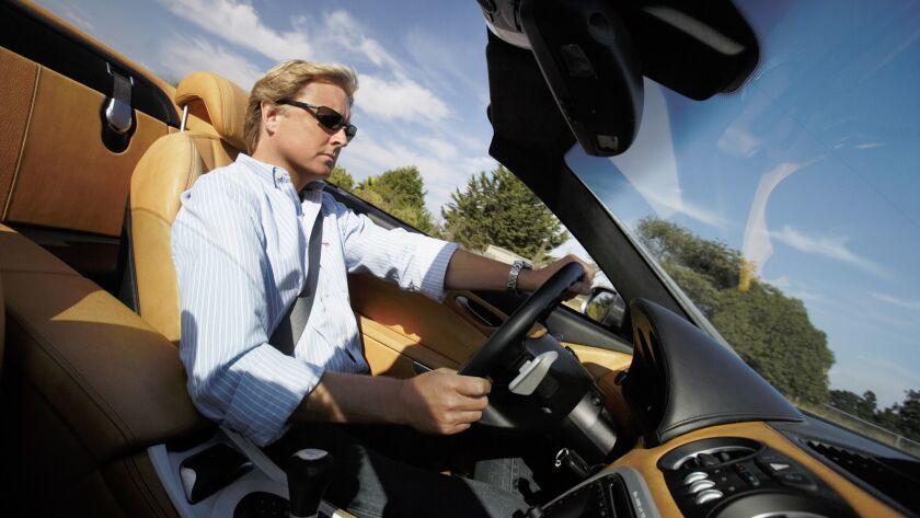 Former BMW and Aston Martin designer Henrik Fisker, behind the wheel of the exotic roadster he desig