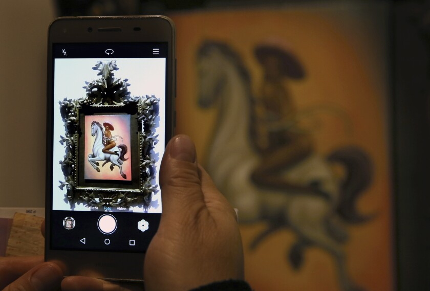 A tourist takes photos of a painting by Mexican artist Fabian Chairez showing Mexican Revolution hero Emiliano Zapata straddling on a horse nude, wearing high heels and a pink, broad-brimmed, during an interview at the Fine Arts Palace in Mexico City, Wednesday, Dec. 11, 2019. Mexico President Andres Manuel Lopez Obrador says he'll ask his culture minister to mediate a dispute over an effeminate painting of Zapata. (AP Photo/Marco Ugarte)