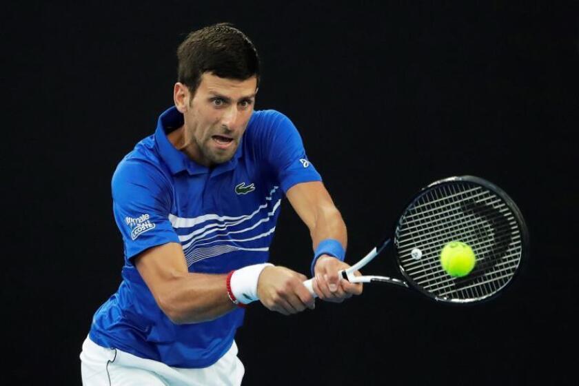 El tenista serbio Novak Djokovic devuelve la bola al japonés Kei Nishikori durante su partido de cuartos de final del Abierto de Australia de tenis, este miércoles en Melbourne. EFE