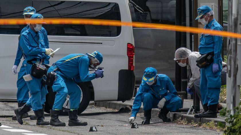 Police forensics officers work at the scene of a mass stabbing May 28 in Kawasaki, Japan.