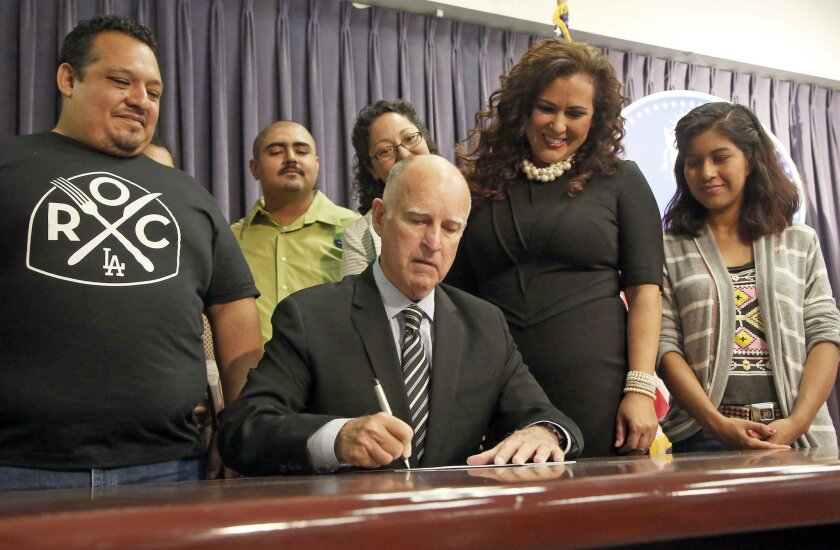 California Gov. Jerry Brown signs a bill mandating the paid leave that supporters say will guarantee that workers don't lose their jobs or their paychecks if they or a family member gets sick, in Los Angeles Wednesday, Sept. 10, 2014. Standing with Brown are, Restaurant Opportunities Center organiz