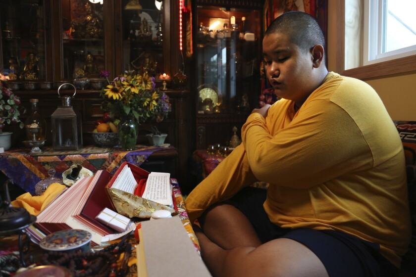Jalue Dorje, 14, says his morning prayers, Tuesday, July 20, 2021, in Columbia Heights, Minn. When he was an infant, Jalue, now 14, was identified as the eighth reincarnation of the lama Terchen Taksham Rinpoche. After finishing high school in 2025, Jalue will head to northern India and join the Mindrolling Monastery, more than 7,200 miles (11,500 kilometers) from his home. (AP Photo/Jessie Wardarski)