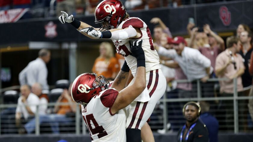 Oklahoma tight end Grant Calcaterra (right) celebrates a touchdown with offensive tackle Cody Ford (left) during the first half of the Big 12 Conference football championship against the Texas on Saturday.