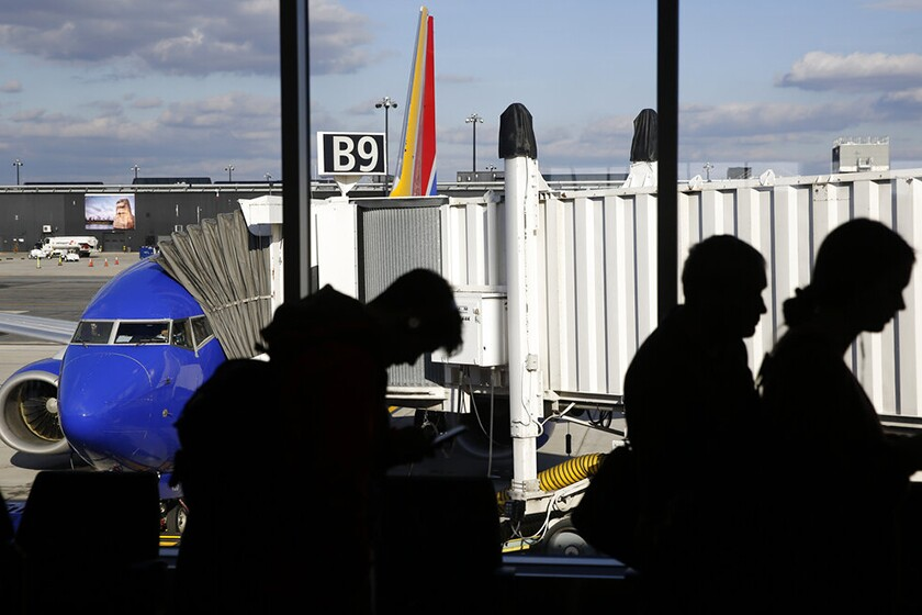 Passengers are seen in silhouette with a plane and passenger boarding bridge in the background.