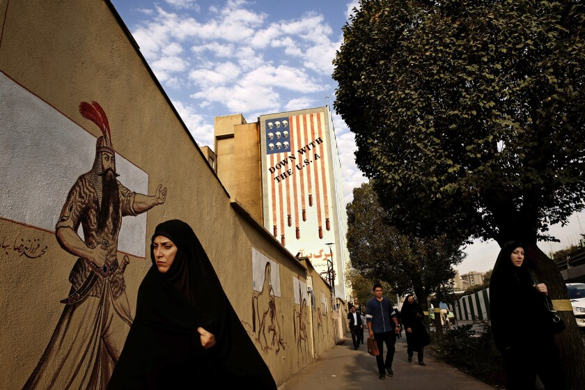 """A mural of a stylized American flag with the words """"Down With the U.S.A."""" looms over a boulevard in central Tehran."""