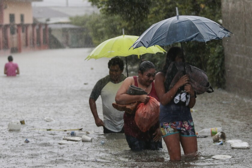 Three people wade through a flooded road carrying some belongings.