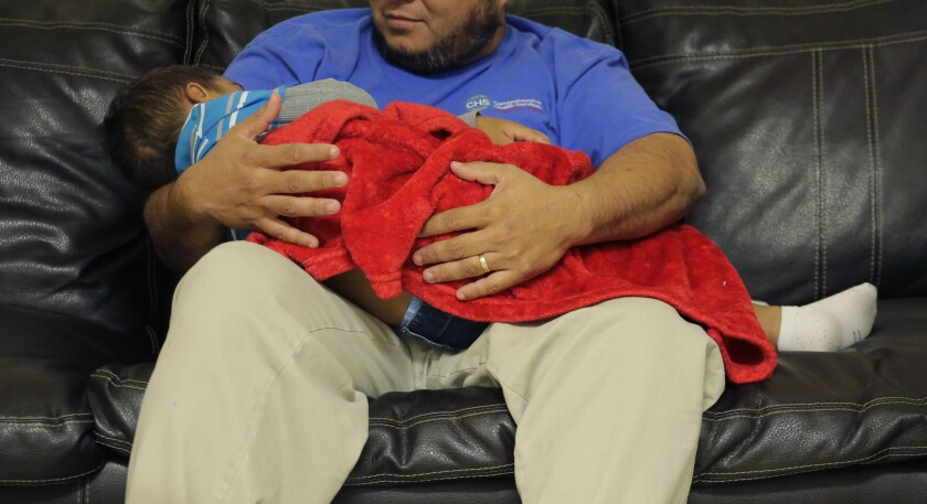 A caregiver holds a migrant toddler