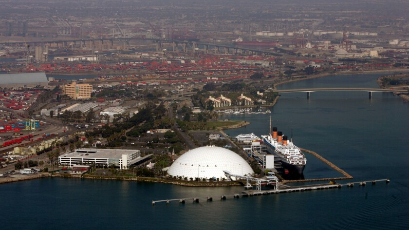 An aerial view of the Queen Mary and the dome that was the former home of the Spruce Goose, with cargo ports in the background, at the Port of Long Beach.