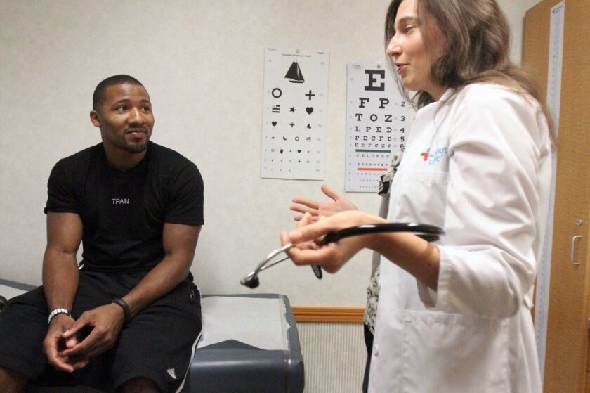 Aaron Hodges sees nurse practitioner Gina Quigley at a CVS Minute Clinic in Los Angeles. Despite a dropoff in patient visits, employer health costs are still climbing by nearly 9%, survey shows.