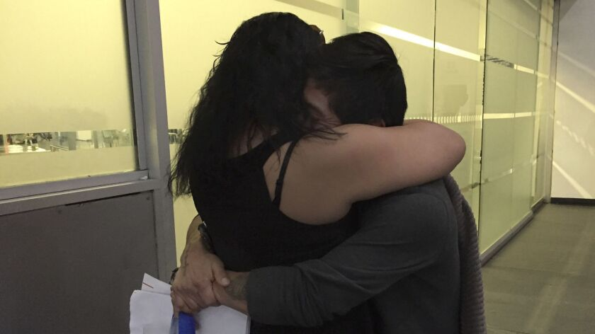 Claudia Arias embraces her husband, Mauricio Marino, who was deported to Mexico.