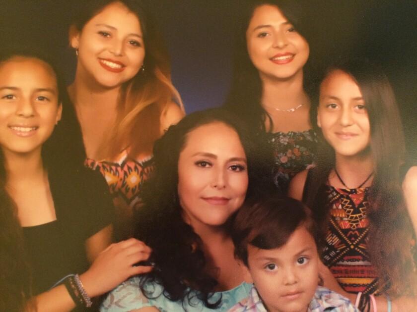 Tomasa posa para una foto familiar con sus hijos.
