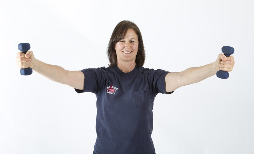 San Diego firefighter Linda Morse performs the Y-raise shoulder stabilization exercise to help prevent injuries.