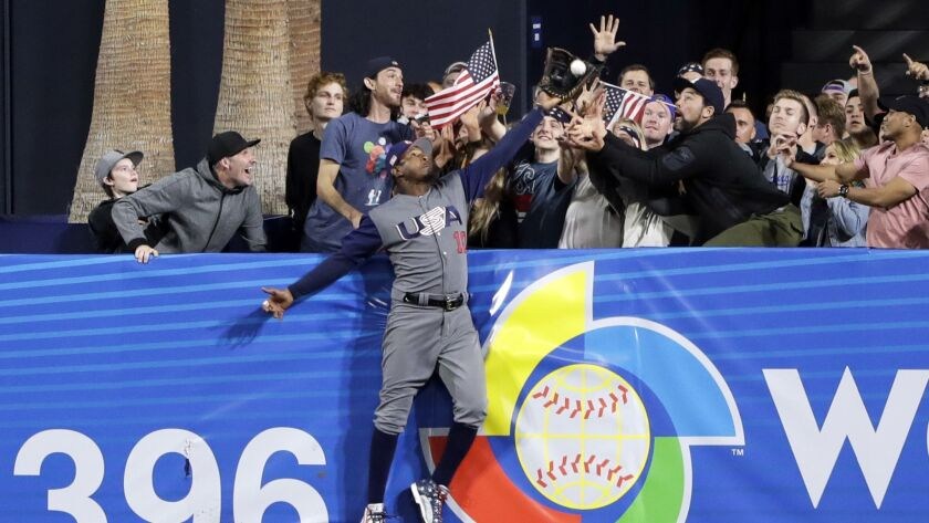 Adam Jones, de Estados Unidos, atrapa una bola sobre el muro para un out de Manny Machado, de Repúbl