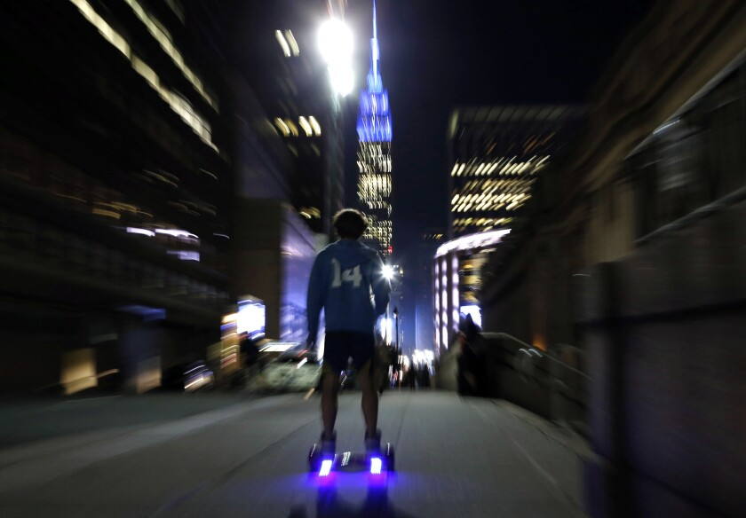 In this 2015 file photo, a young man rides a hoverboard along a Manhattan street.
