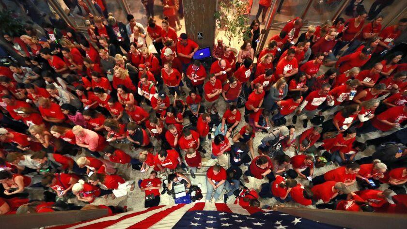 Teachers crowd the lobby of the Arizona Senate as Arizona legislature debate a budget negotiated by