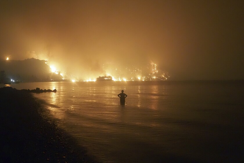 A person stands in the water watching a fire burn up the coast.