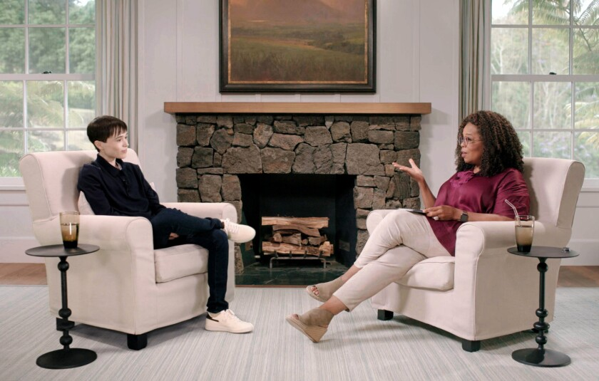 Elliot Page and Oprah Winfrey chat in living room armchairs.