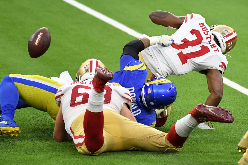 Rams defensive lineman Aaron Donald forces a fumble as he tackles 49ers running back Raheem Mostert.