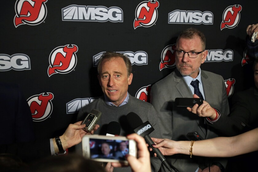FILE - In this Jan. 12, 2020, file photo, New Jersey Devils owner Josh Harris, left, announces interim general manager Tom Fitzgerald, right, to replace Ray Shero prior to an NHL hockey game in Newark, N.J. The New Jersey Devils' season began with great expectations with return of an injured MVP, a trade for a Norris Trophy-winning defenseman and the addition of a second No. 1 overall draft pick in three years. It also ended with high hopes. In between was ugly. (AP Photo/Adam Hunger, File)