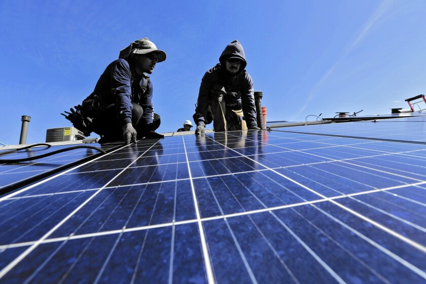 Workers install a rooftop solar system on a Van Nuys home. Clean energy advocates say policies for addressing climate change can help create jobs.