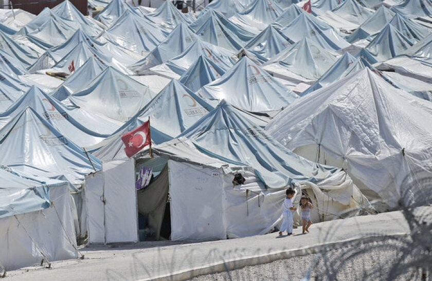 Children walk past tents at a Syrian refugee camp in Yayladagi, Turkey.