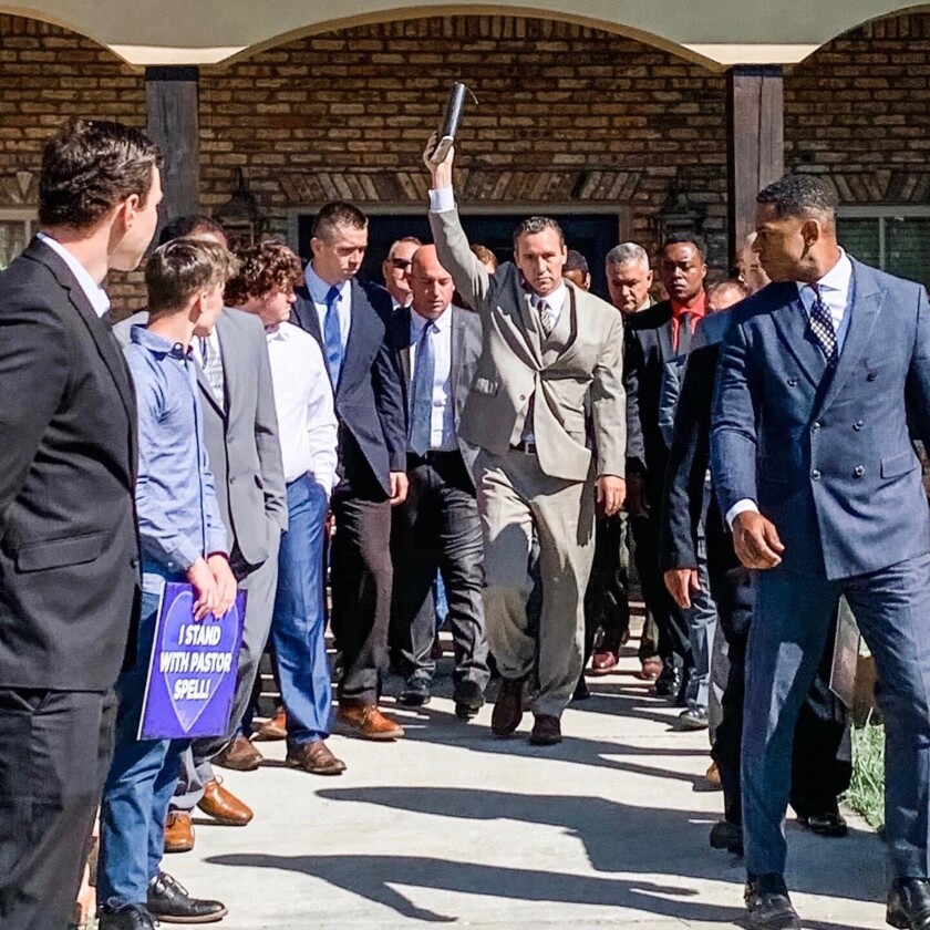 Rev. Tony Spell leaves his home in suburban Baton Rouge, La., where he has been held under house arrest, and walks with members of his congregation to lead Sunday-morning service at Life Tabernacle Church next door.