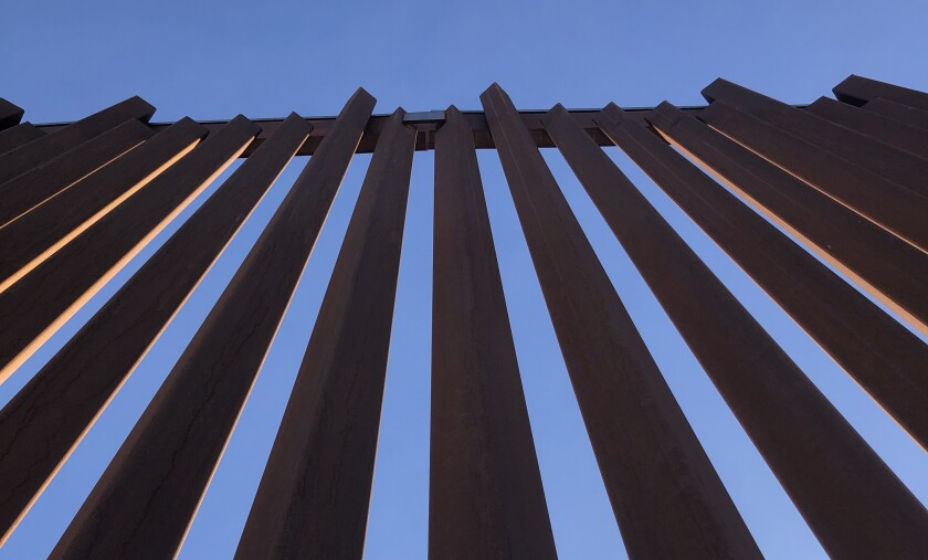 Metal bars of a border barrier stretch up toward a clear blue sky