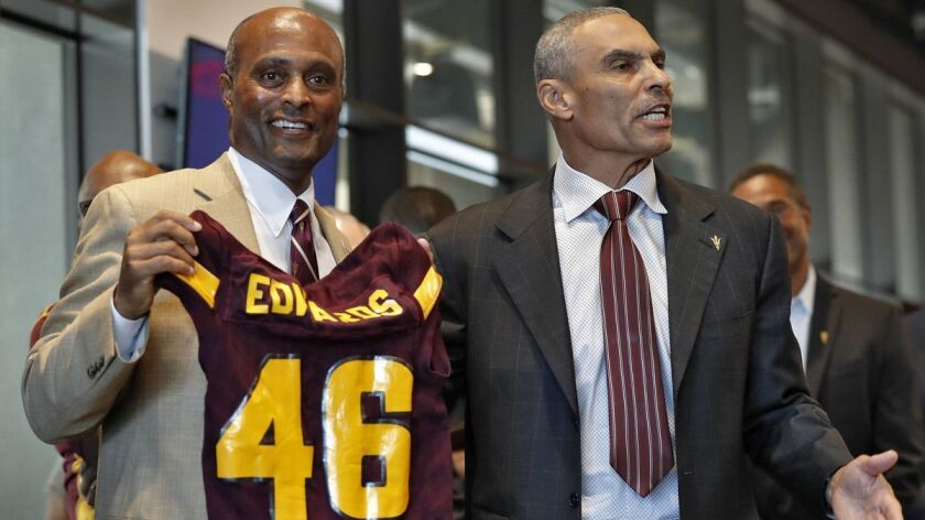Newly appointed Arizona State University NCAA college football head coach Herman Edwards, right, hol